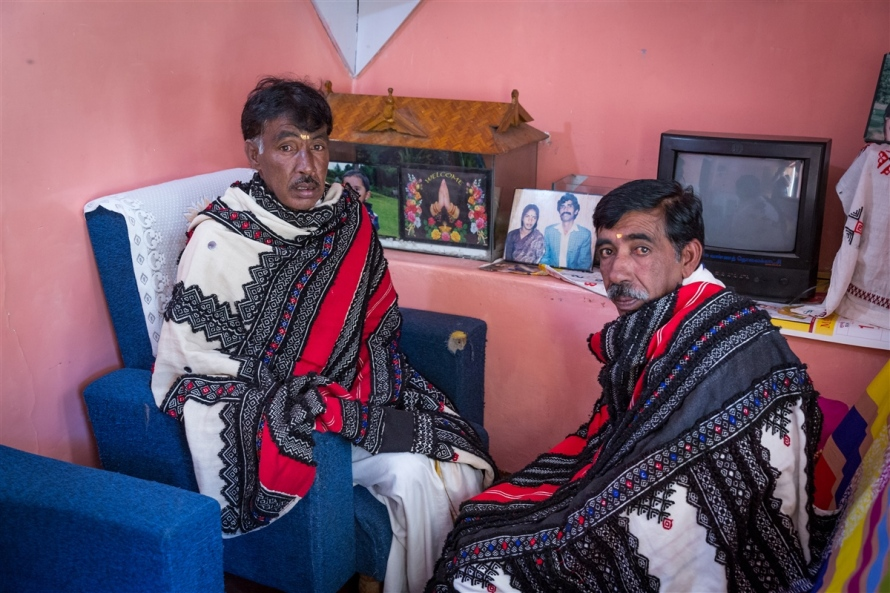 Two Toda Tribe elders sitting in a modern house construction